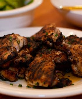 grilled chicken thighs on a plate seasoned with lemon and olive oil